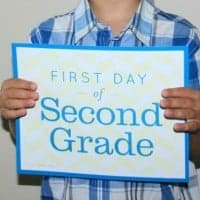 child holding a first day of second grade sign