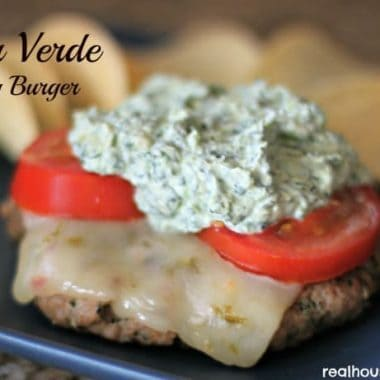 salsa verde turkey burger topped with cheese, tomato slices, and dip