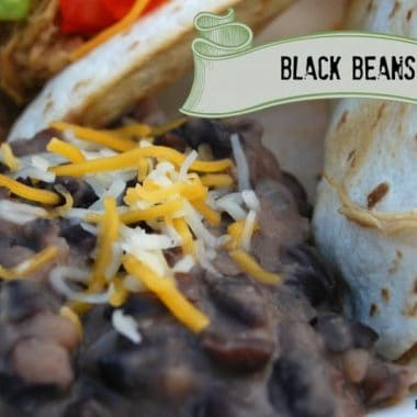 close up of black beans topped with shredded cheese