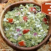 avocado and feta dip with crackers on a platter