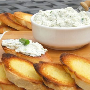 herbed ricotta bruschetta in a bowl with toasted bread slices