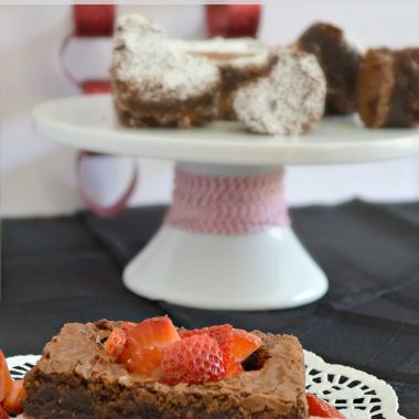 symphony brownies with sliced strawberries on a doily