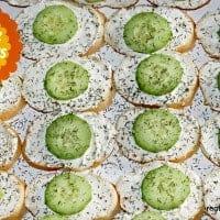 open faced cucumber sandwiches on a platter