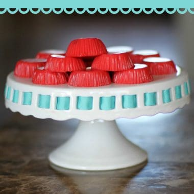 Cherry jell-o yogurt bites on a elevated cake plate with blue trim