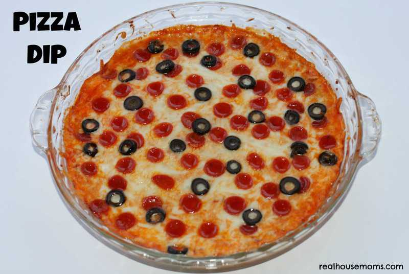 pizza dip in a clear bowl topped with olives and pepperoni