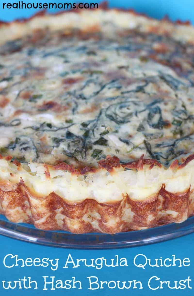 cheesy arugula quiche with has brown crust on a plate