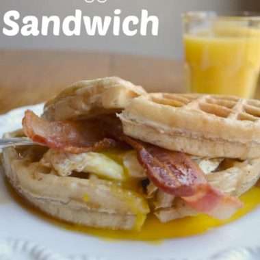 bacon, egg waffle sandwich on white plate with glass of orange juice