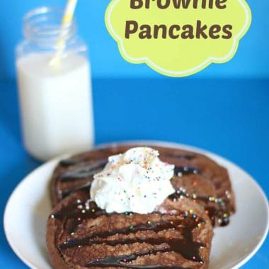brownie pancakes topped with whipped cream on a plate and a glass of milk