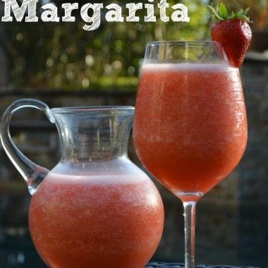 strawberry margarita in a pitcher and glass garnished with strawberry