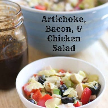 artichoke, bacon & chicken salad in a white bowl with dressing in mason jar
