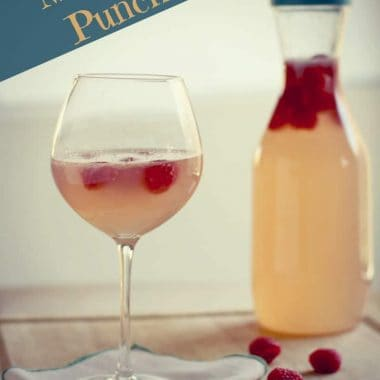 moscato punch in wine glass and pitcher garnished with raspberries