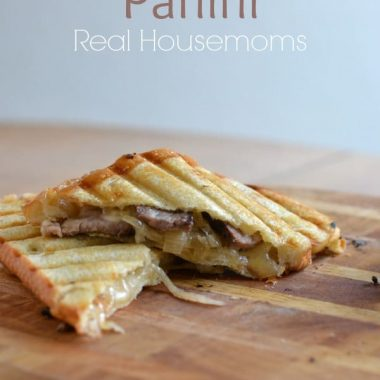steak & onion panini on wooden cutting board
