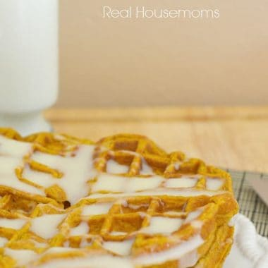 pumpkin spice waffles stacked with a cream cheese glaze