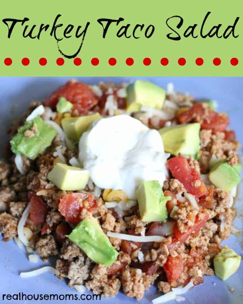 turkey taco salad topped with avocado and sour cream