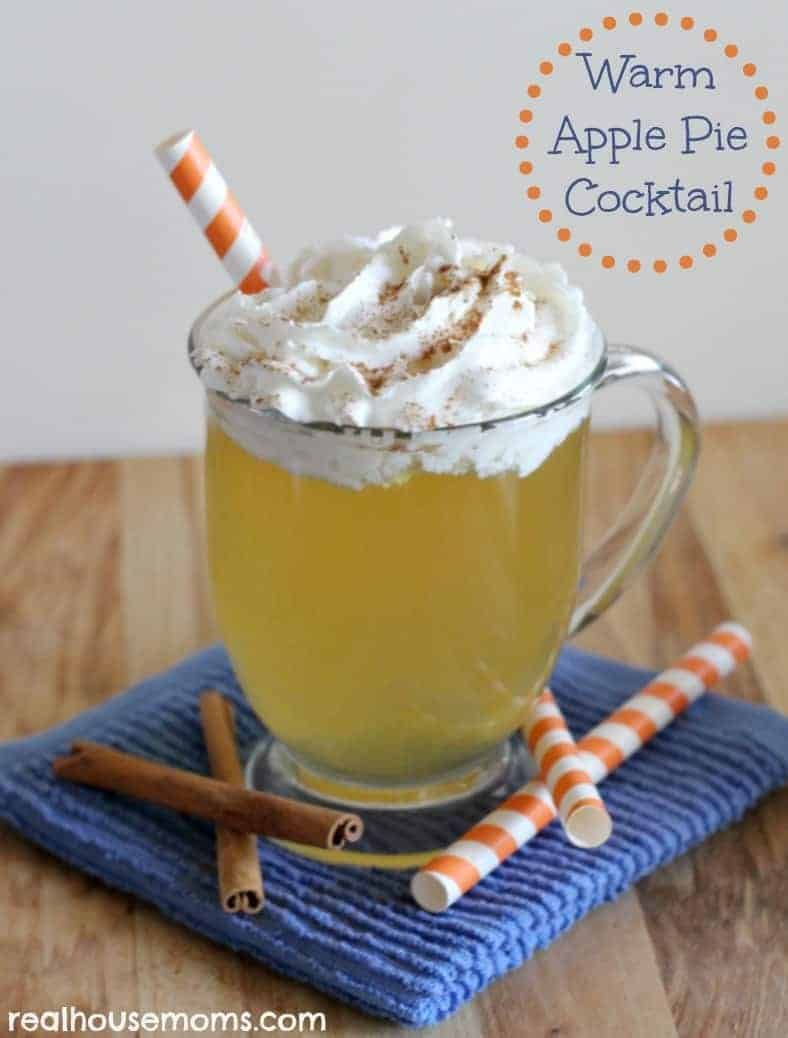 warm apple pie cocktail in a mug topped with whipped cream