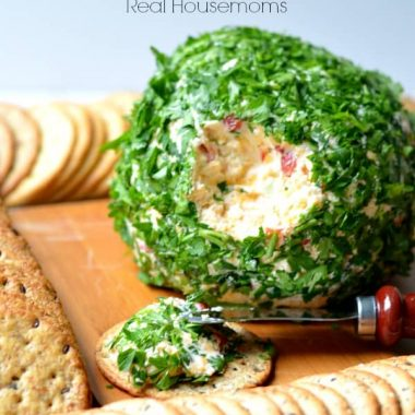 onion and bell pepper cheese ball on a cutting board with crackers