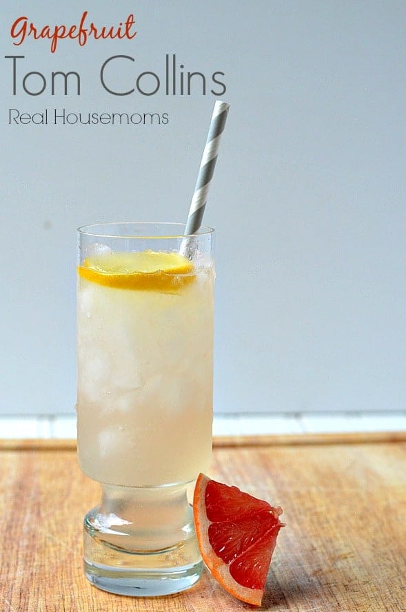 grapefruit tom collins in a glass with lemon slice and grapefruit wedge
