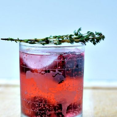 thyme berry sparkler drink in a glass topped with thyme