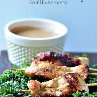 chicken satay over a bed of kale served with dipping sauce