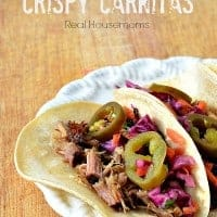 three tortillas stuffed with slow cooker crispy carnitas and topped with jalapeno slices