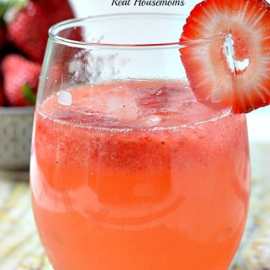 spiked strawberry shortcake drink in a glass with strawberry garnish