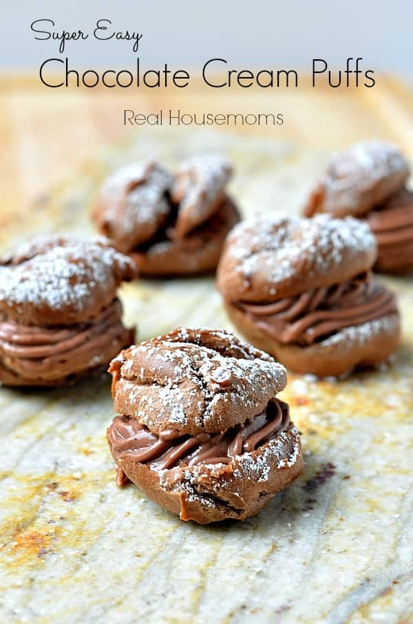 chocolate cream puffs topped with powdered sugar on a platter