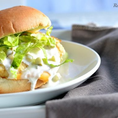 fish fillet sandwich topped with shredded lettuce and tartar sauce on a white plate