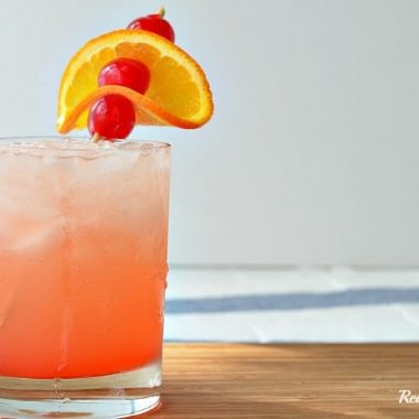 tropical sunset drink in a glass with fruit garnish