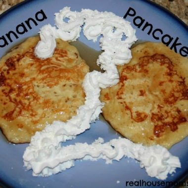 banana pancakes with syrup and a numeral 2 made out of whipped cream