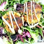 spring mix salad topped with quinoa crab cakes