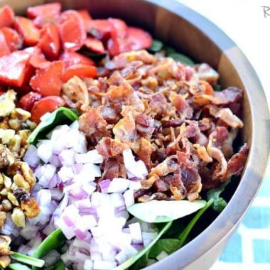Spinach Bacon and Strawberry Salad displayed in a wooden sharing bowl