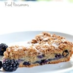 Slice of Very Berry Coffee Cake displayed on a white sharing plate topped with blueberries