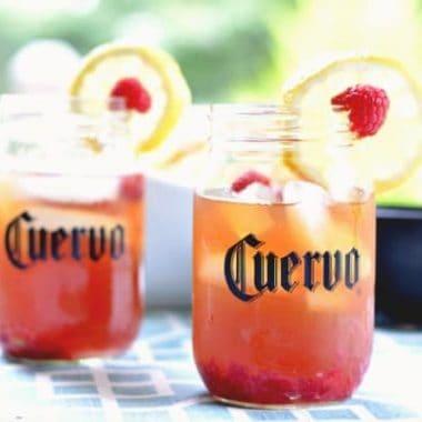 raspberry lemon iced teagarita in mason jars garnished with lemon and rasberries