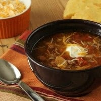 Slow Cooker Three Bean Chili displayed with a side of shreaded cheese