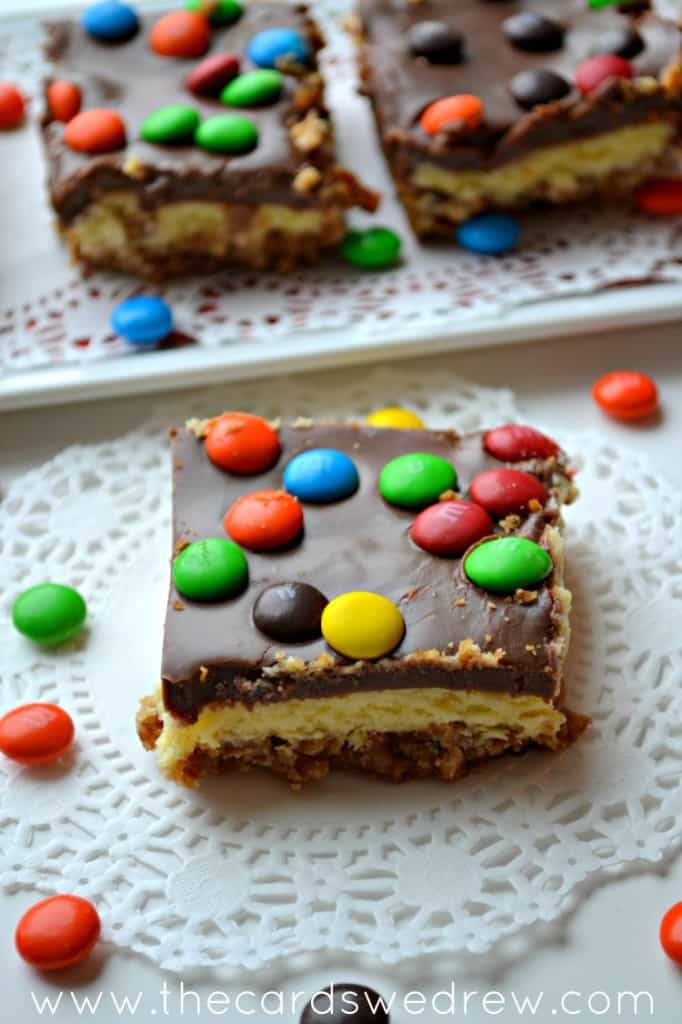 M&M CHEESECAKE BARS WITH PRETZEL CRUST AND CHOCOLATE FROSTING