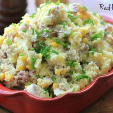 Warm Bacon Corn Smashed Potato Salad served in red baking dish