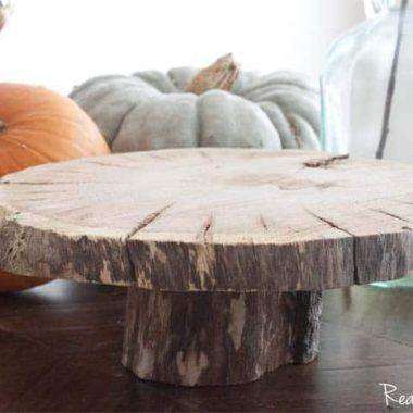 DIY Wood Slice Pedestal Cake Plate. With fall pumpkins in the background.