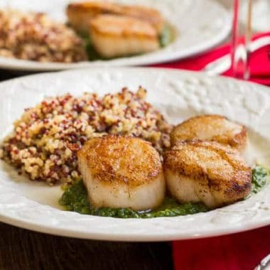 Pan Seared Scallops with creamy pesto sauce served on a white dish served with a side of rice