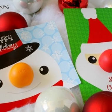 "chapstick Holiday Cards. two cards one of snowmans face on a blue card. with EOS orange chapstick as his nose Card says ""HAPPY HOLIDAYS"" second card santa face on a green card. with EOS red chapstick as his nose Card says ""Merry christmas"" cards is laying on fake snow with white and red orniments in the background"