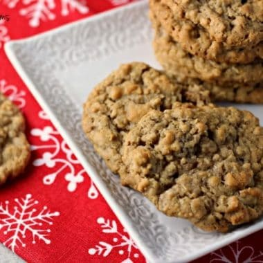 Spiced Oatmeal Raisin Cookies served on a white dish with a festive christmas table cloth in background