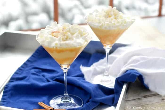 eggnog martini topped with whip cream served ina martini glass.photo shows two martinis on a serving tray