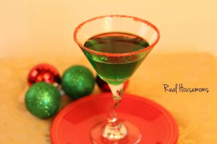 mistletoe mint martini, A green cocktail served in a martini glass, displayed on a red serving tray with red sugar on the rim