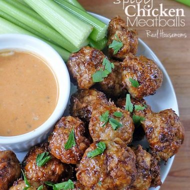 Spicy Chicken Meatballs on a platter with dipping sauce & celery