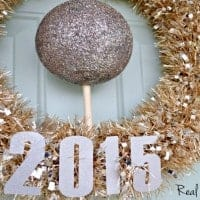 "New Year's Wreath. Festive gold and silver wreath with a silver ball in the middle. wreath says ""2015"""