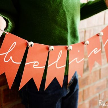 Printable believe banner, child holding banner, Banner is red with red and white string with bells at the top