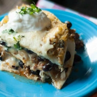 Black Bean Chorizo Enchilada Casserole topped with sour cream