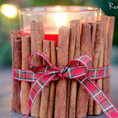 Cinnamon Stick Holiday Candle. Cinnomon sticks arranged to make candle holder. plaid christmas bow tied around candle holder. Red candle inside