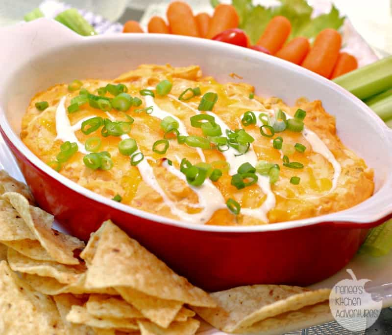 Creamy Buffalo Ranch Chicken Dip served in a red and white baking dish with a side of chips, carrots and celary