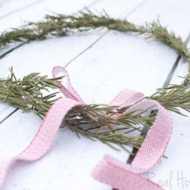 DIY Rosemary Wreaths, Rosemary branches arranged to make Wreath. Red and white bow on top of wreath