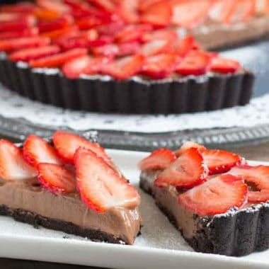 Strawberry Chocolate Tart topped with sliced strawberries, two slices displayed on a serving dish with tart in background